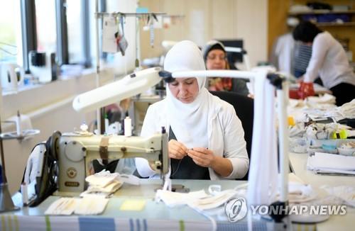 18일 독일 에센의 한 병원에 설치된 작업장에서 마스크를 생산하고 있다.