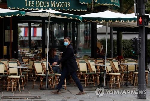 마스크 쓴 채 프랑스 파리의 식당 앞을 지나는 여성