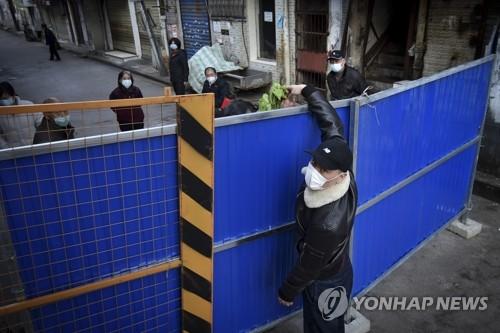 주택 봉쇄 바리케이드 너머로 식료품 전달하는 중국인