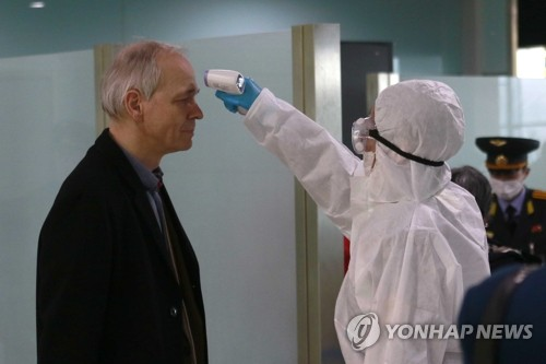 북한 평양국제공항 떠나기 전 체온 재는 외국인