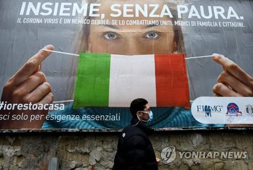 이탈리아 코로나19 포스터 앞 지나는 남성