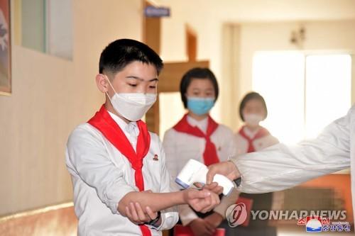 복도에서 마스크 쓰고 체온 재는 북한 중학생들